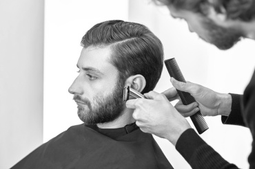 Grooming the beard. Barbershop. Man hairdresser doing haircut beard adult men in the men's hair salon. Hairdressers in the workplace. Barber. Grooming the beard. Barbershop.